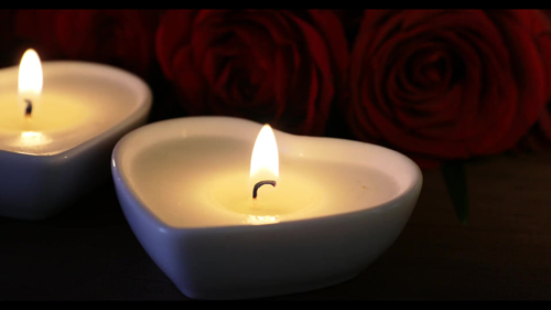 Close up of Heart Shaped Candles Burning in Front of Red Roses