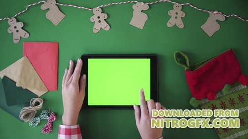 Footage - Woman finger swipe images right and left, tapping on green screen of tablet device